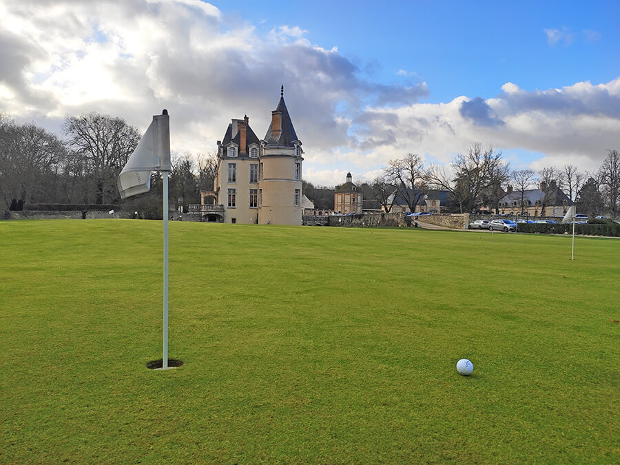 the golf course has a beautiful putting practice in front of the castle